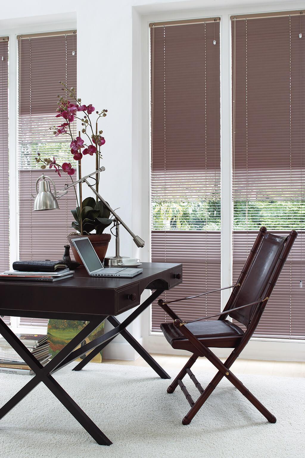 Beige Alu-Jalousie an deckenhohen Fenstern mit Ledertisch im Vordergrund