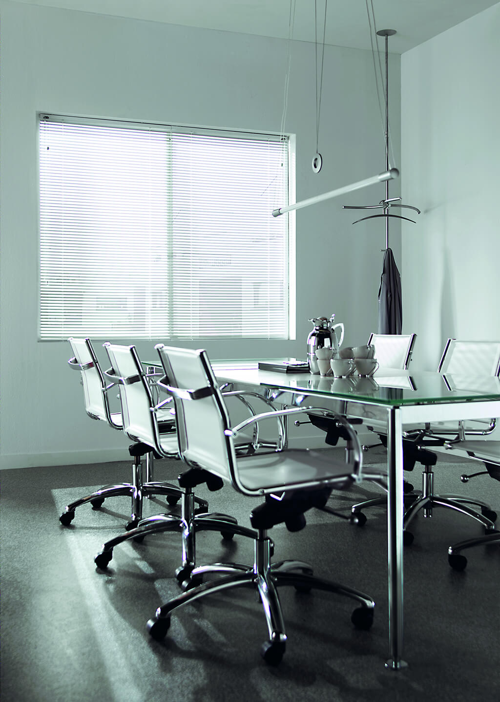 Weiße Alu-Jalousie in einem schlichten Konferenzraum mit Glastisch und weißen Stühlen