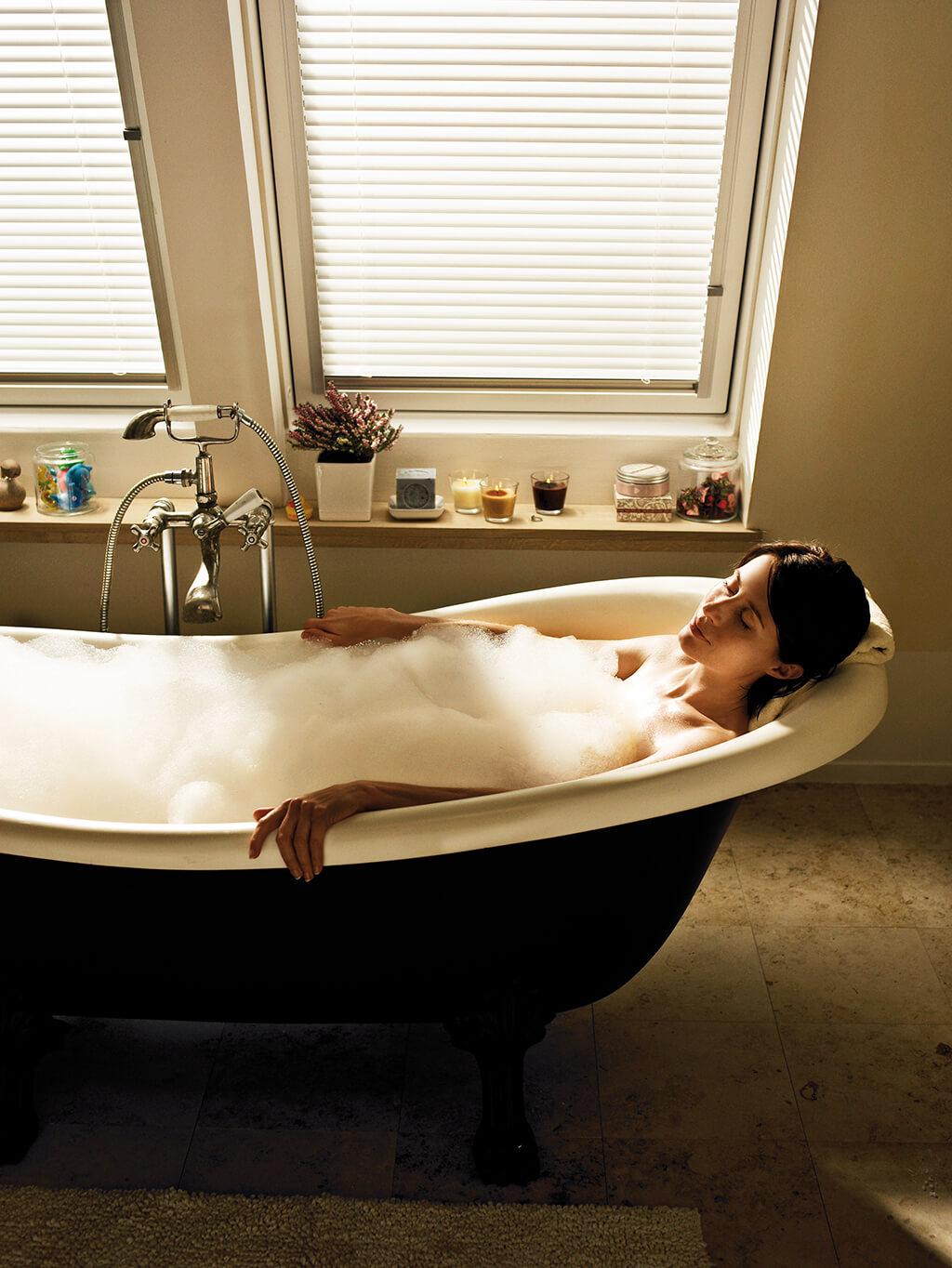 Weiße Alu-Jalousie am Dachfenster im Badezimmer mit freistehender Badewanne