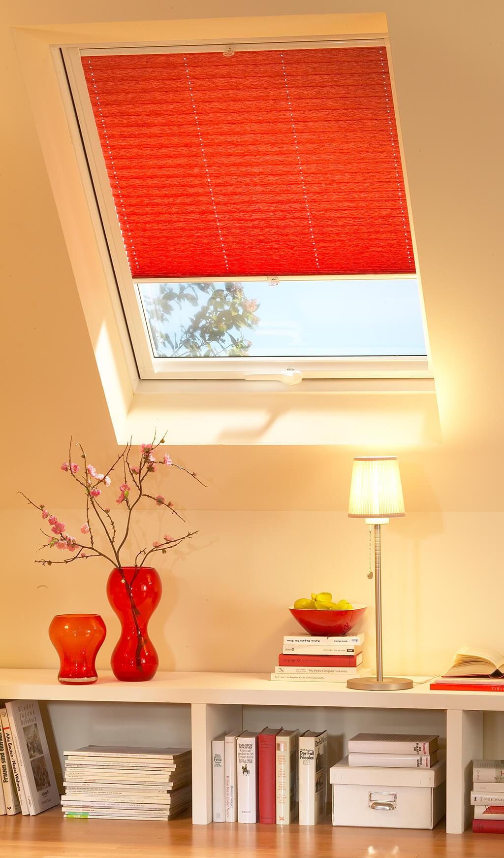 Rotes Plissee am Dachfenster im Wohnzimmer von unten leicht geöffnet