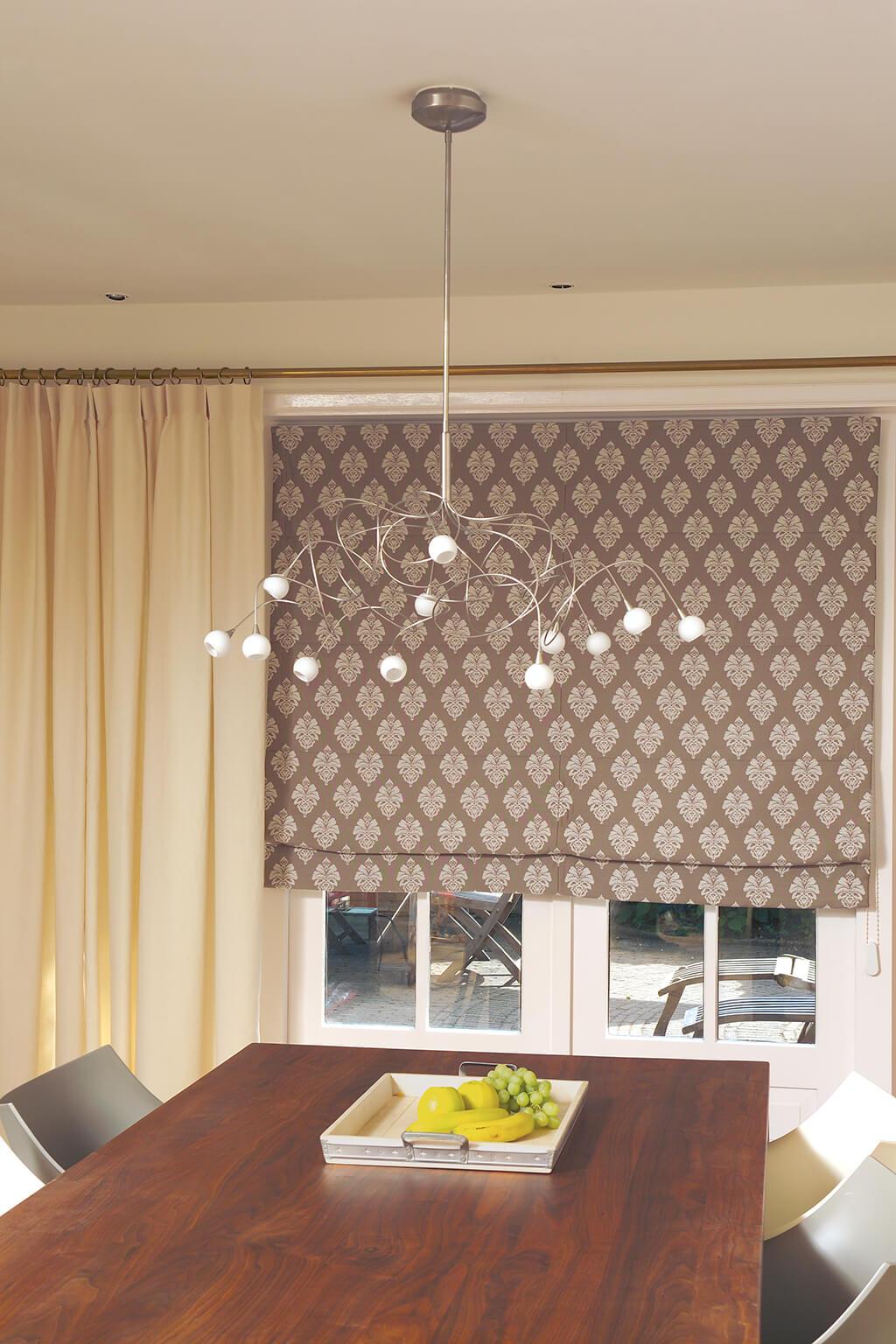 Gemustertes Faltrollo in braun-beige und beiger Gardine am Esszimmerfenster