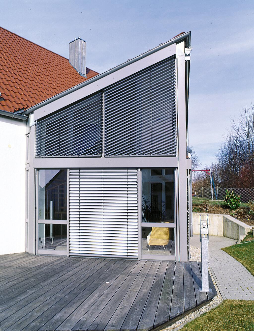 Silberne Außenjalousie aus Aluminium an großen Schrägfenstern im Wintergarten
