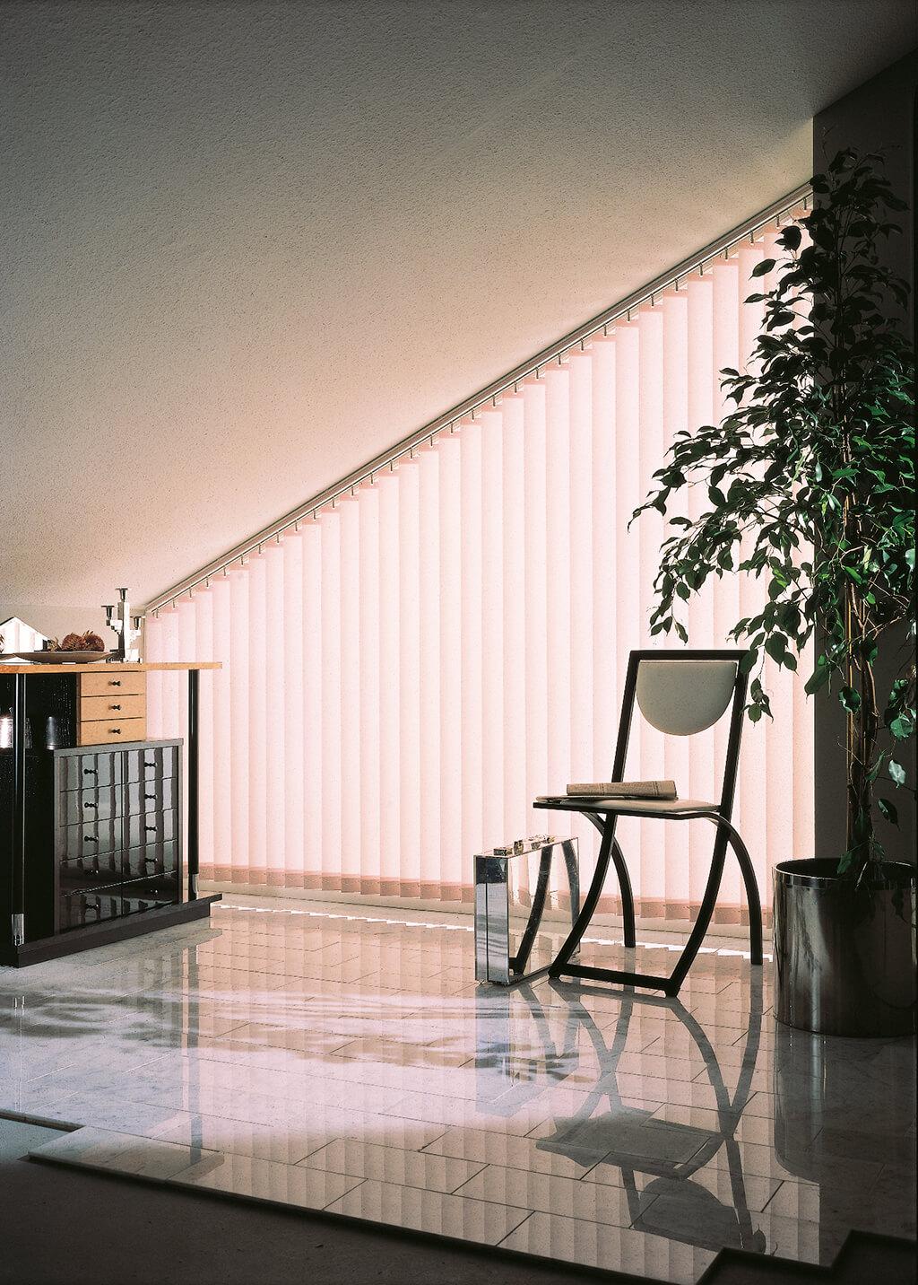 Weißer Lamellenvorhang am Fenster in der Dachschräge