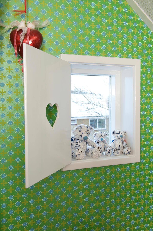 Kleines Fenster mit Kuscheltieren und einem weißen Fensterladen mit Herzausschnitt