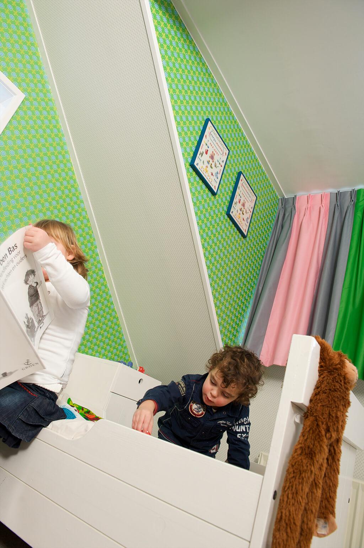 Spielende Kinder auf dem Boden und Bett mit einer mehrfarbigen Gardine im Hintergrund