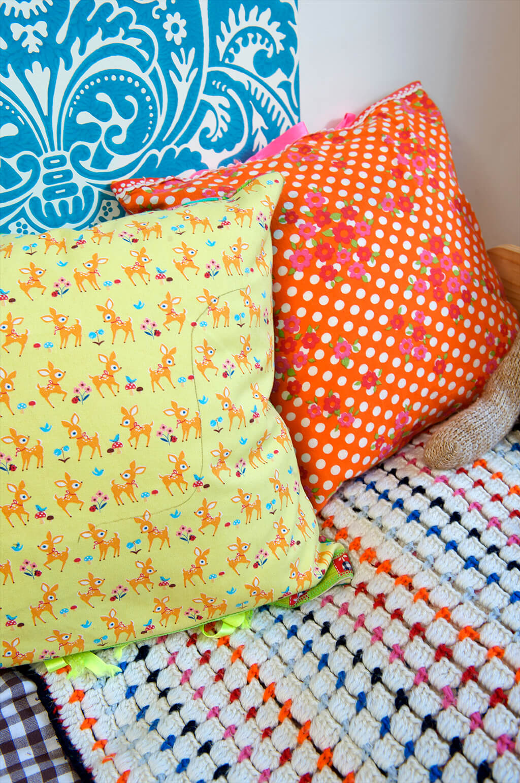 Detailaufnahme von gemusterten Kissenbezügen mit Bambi- und Blumenmotiven im Kinderzimmer