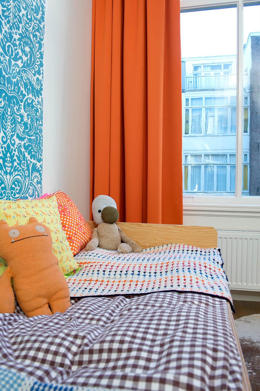 Kinderbett mit Kuscheltieren und orangener Gardine mit doppelter Falte im Hintergrund