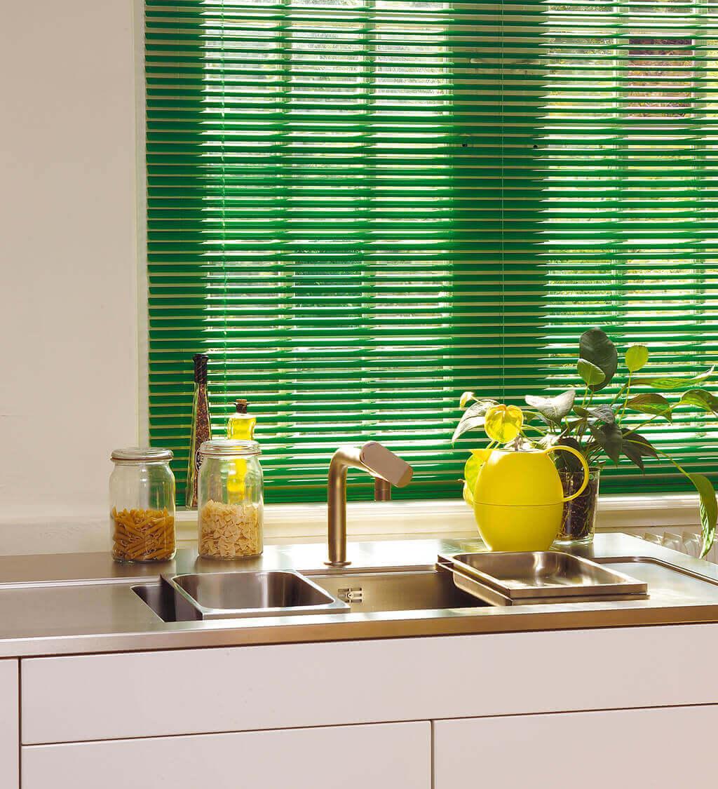 Grüne Alu-Jalousie mit schmalen Lamellen am Küchenfenster
