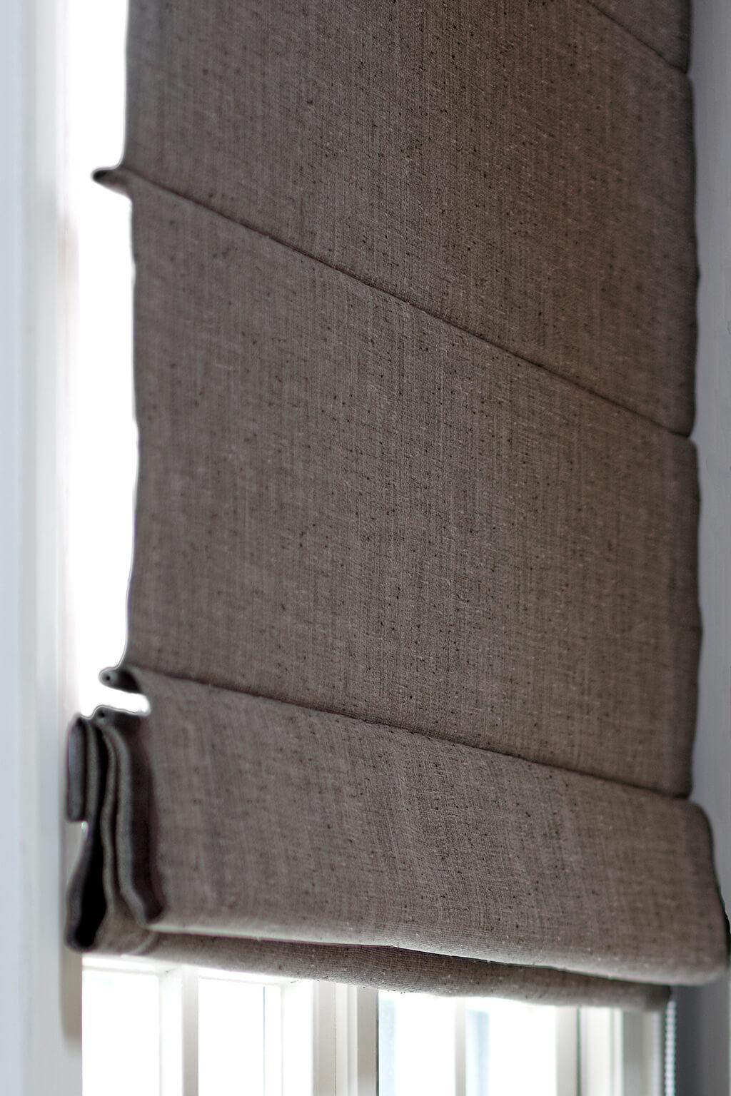 Detailaufnahme von einem grauen Faltrollo mit Querstreben
