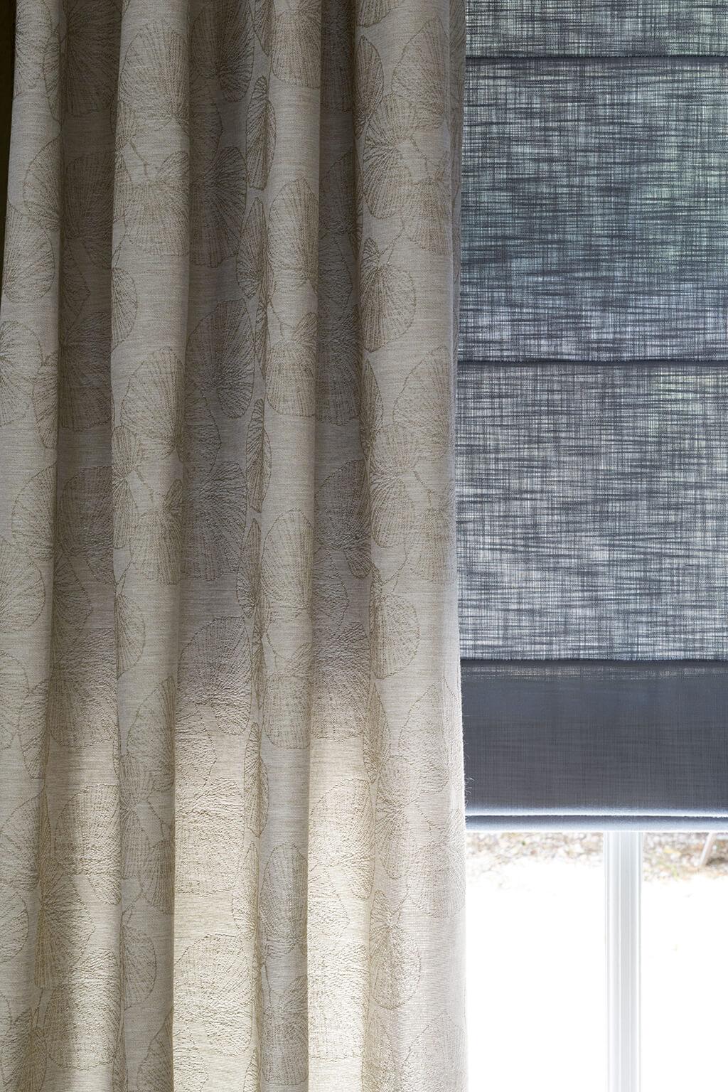 Detailaufnahme von einem grauen Faltrollo mit Querstreben in Kombination mit einer beigen Gardine
