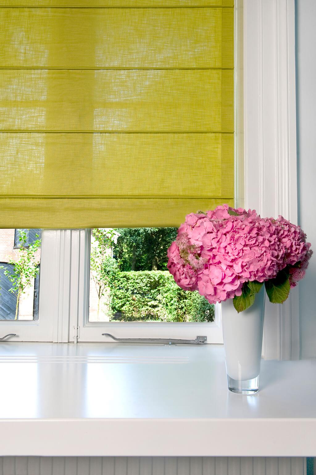 Grünes Faltrollo mit Querstreben und eine Vase mit rosa Hortensien