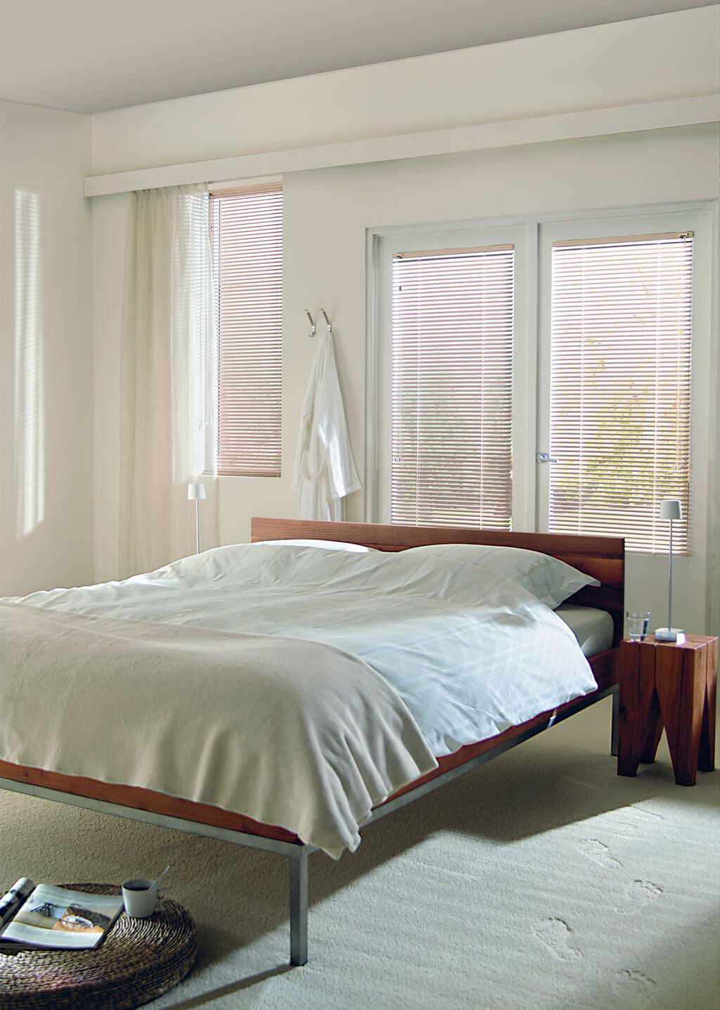 Beige Alu-Jalousie mit schmalen Lamellen an verschieden großen Fenstern im Schlafzimmer