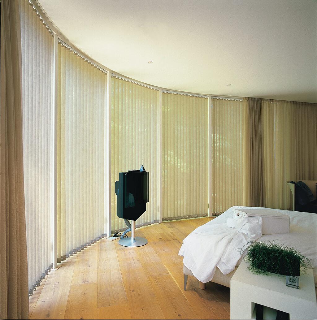 Beiger, gebogener Lamellenvorhang im Schlafzimmer in Kombination mit einer Gardine aus transparentem Stoff