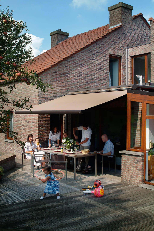 Familie und Freunde beim Essen auf der großen Terrasse unter der braunen Markise