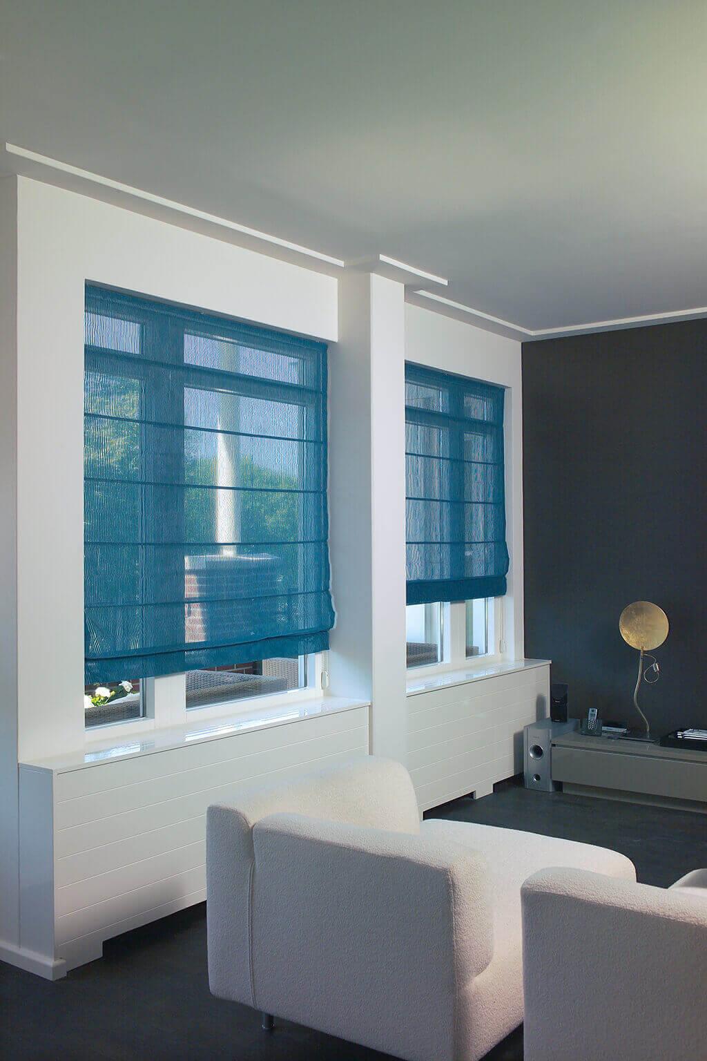 Blaues, lichtdurchlässiges Faltrollo an Fenstern im Wohnzimmer mit Blick auf die Terrasse