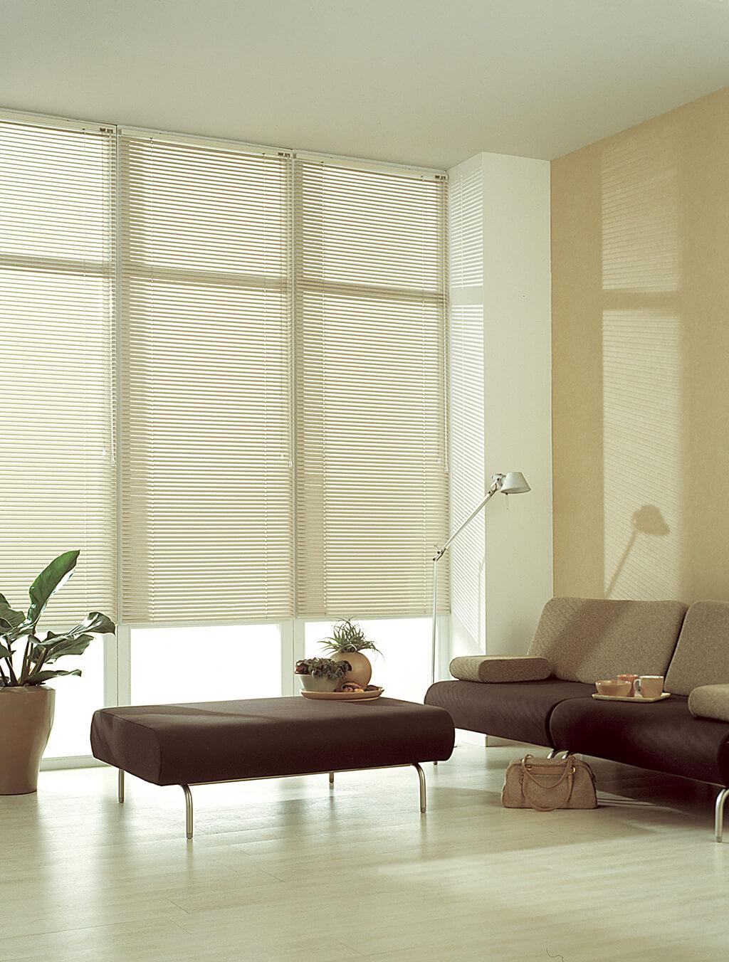 Weiße Alu-Jalousien an deckenhohen Fenstern im Wohnzimmer mit braun-beigen Möbeln