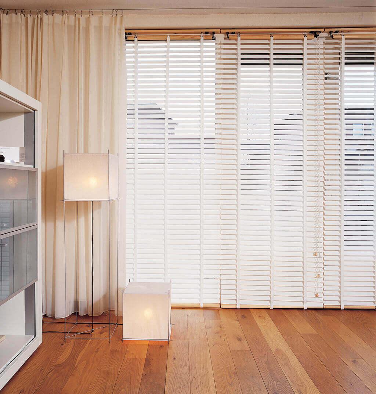 Weiße Holzjalousien an deckenhohen Fenstern in Kombination mit einer weißen Gardine im Wohnzimmer