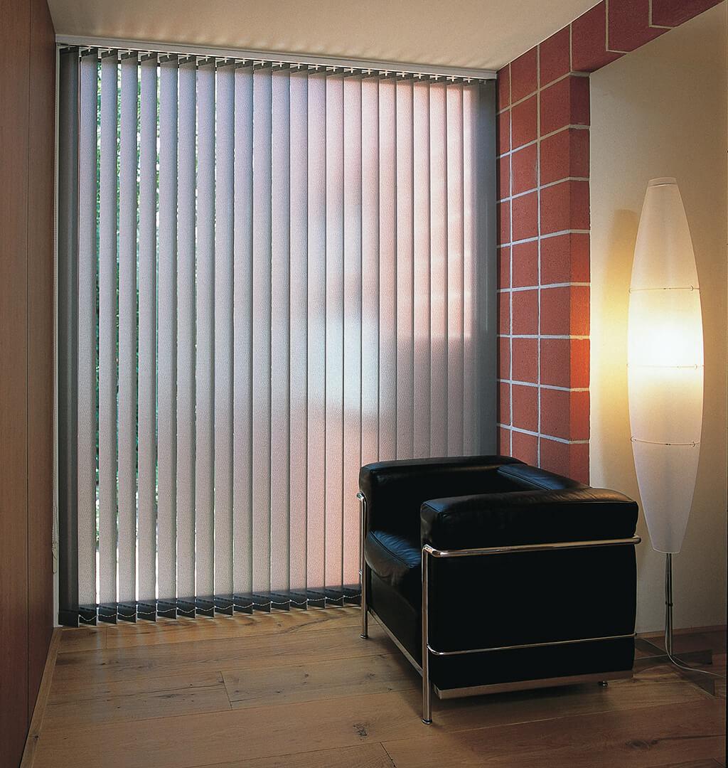 Grauer Lamellenvorhang am großen Fenster hinter schwarzem Ledersessel