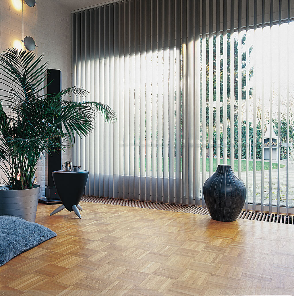 Weißer Lamellenvorhang am Wohnzimmerfenster mit Blick in den Garten
