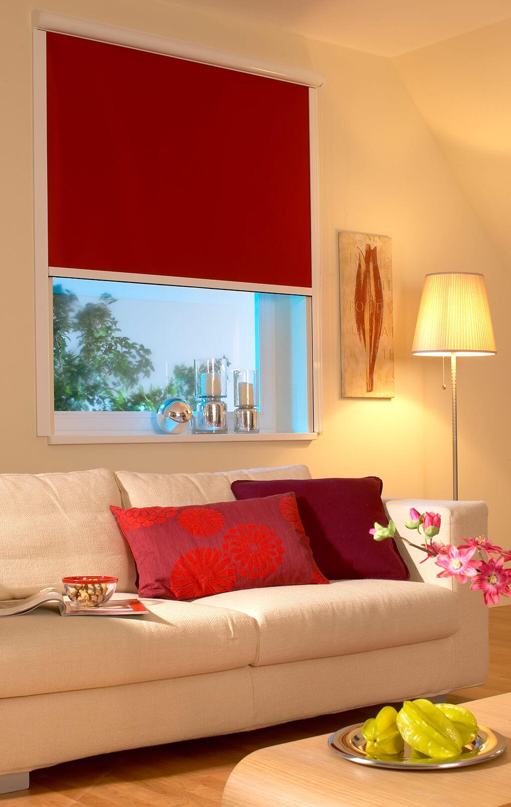 Rotes Verdunkelungsrollo mit seitlichen Schienen im Wohnzimmer
