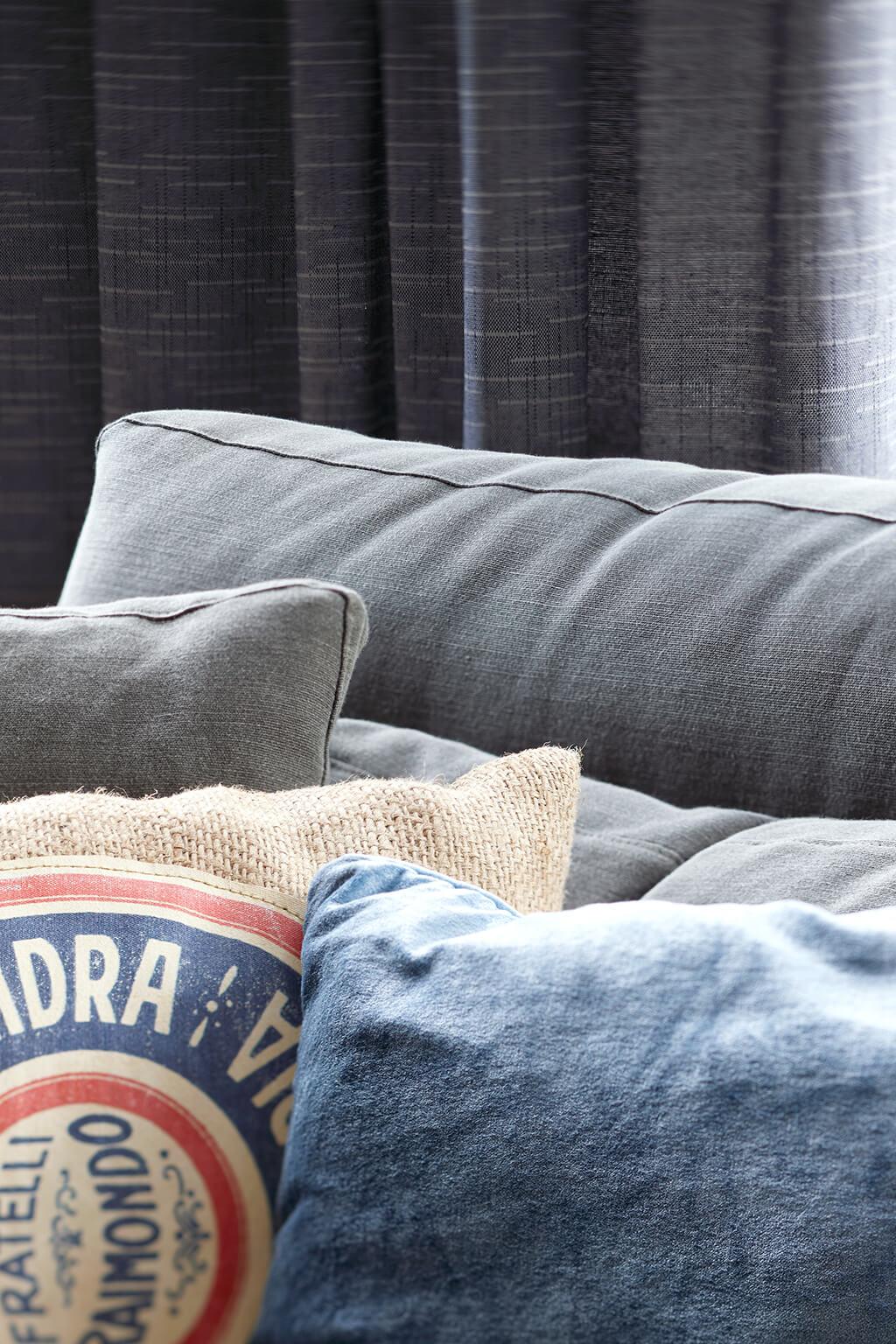 Detailaufnahme von einer grau-blauen Gardine hinter einer grauen Couch im Wohzimmer