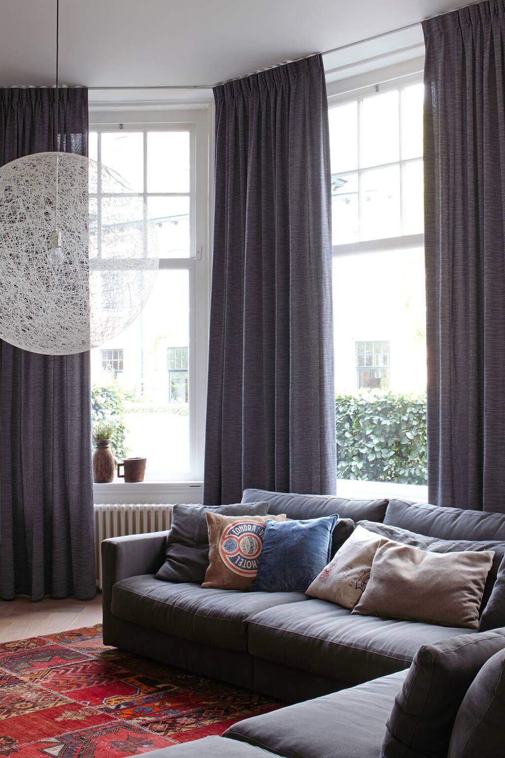 Grau-blaue Gardine mit doppelter Falte im Wohnzimmer hinter gemütlicher Couchecke