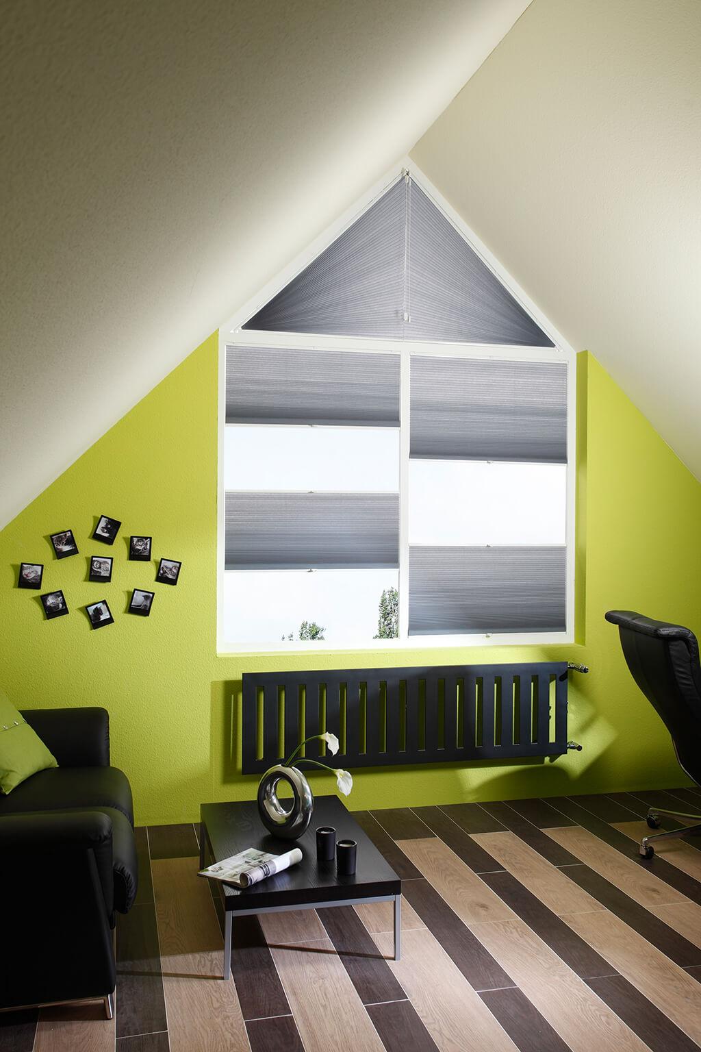 Graue Wabenplissees an Fenstern im Dachstuhl mit verschiedenen Fensterformen