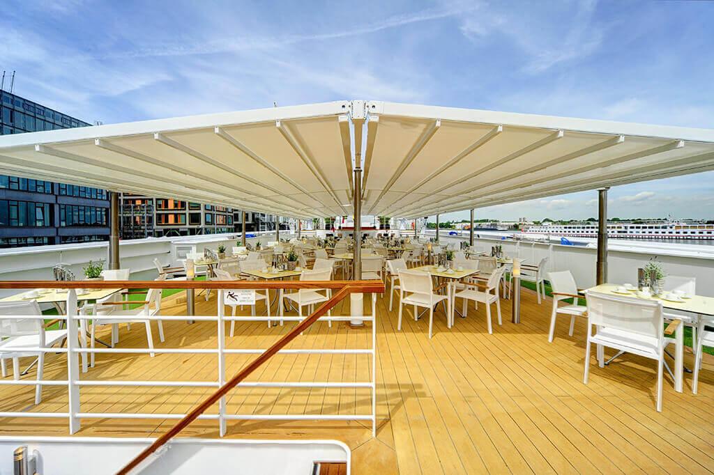 Weiße Pergola SUNRAIN S auf großem Schiffsdeck mit Gastrobereich