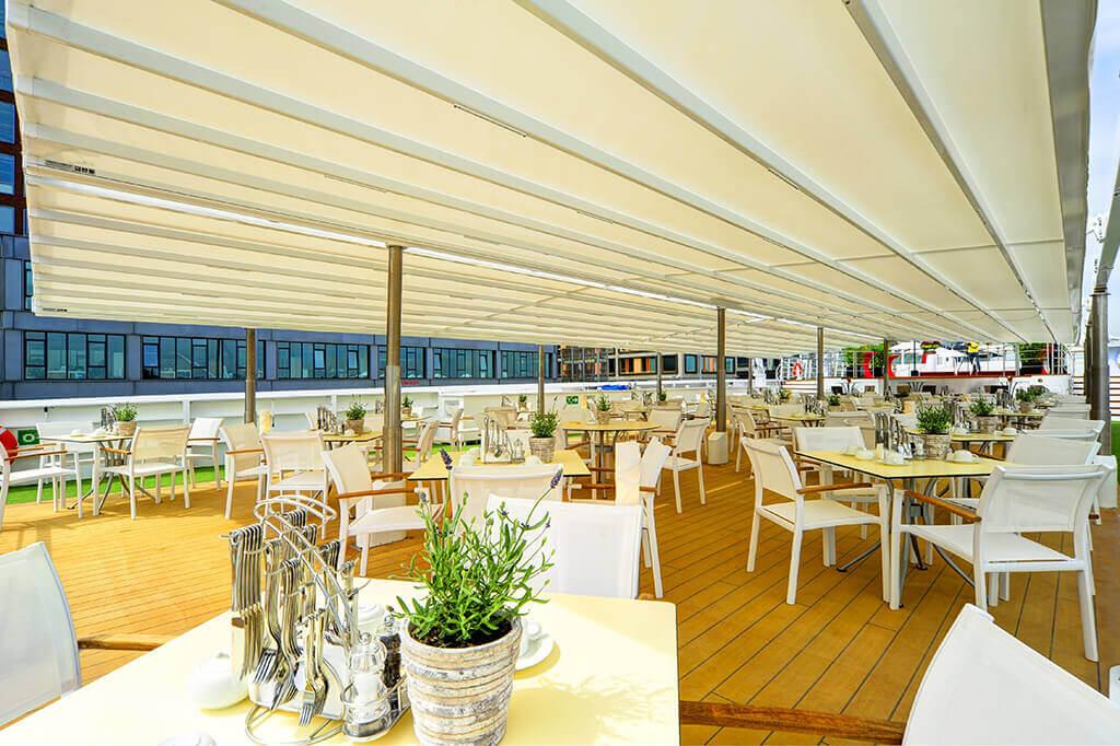 Weiße Pergola SUNRAIN S als Überdachung für den Gastro-Bereich eines Schiffs