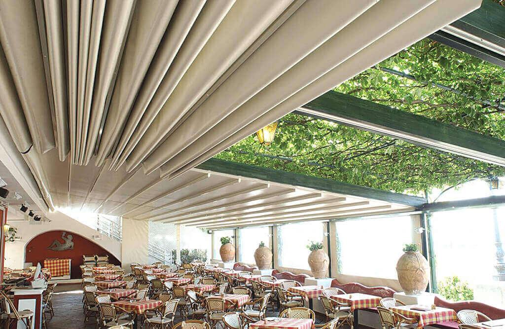 Beige Pergola SUNRAIN S geschlossen und halboffen als Überdachung einer Gastro-Terrasse