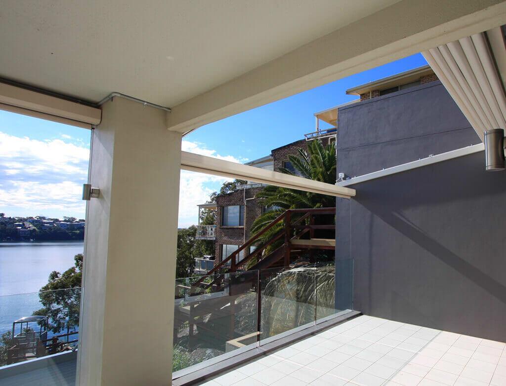 Geschlossene Pergola SUNRAIN S auf einer großen Terrasse mit Meerblick