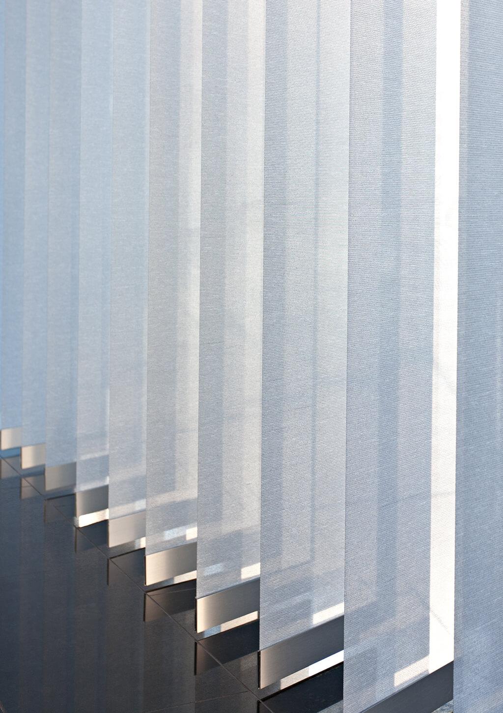 Detailaufnahme: Breiter Lamellenvorhang in weiß mit silberner Aluminiumschiene am Stoffende