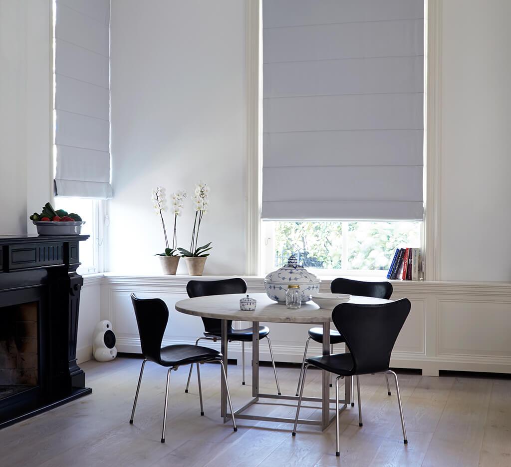 Dezente weiße Faltrollos zur Verdunklung an hohen Fenstern
