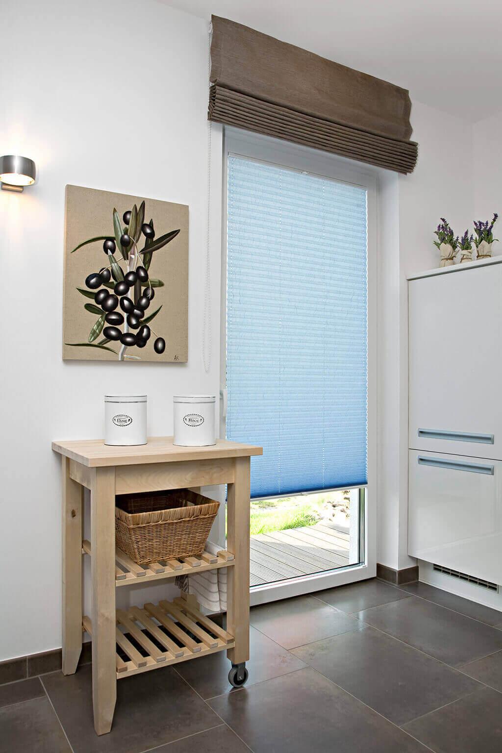 Hellblaues Plissee an der Küchentür, kombiniert mit braunem Faltrollo