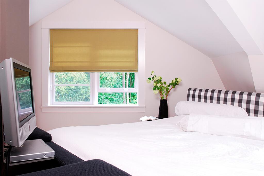 Cremefarbenes Faltrollo in der Schlafzimmer Fensternische
