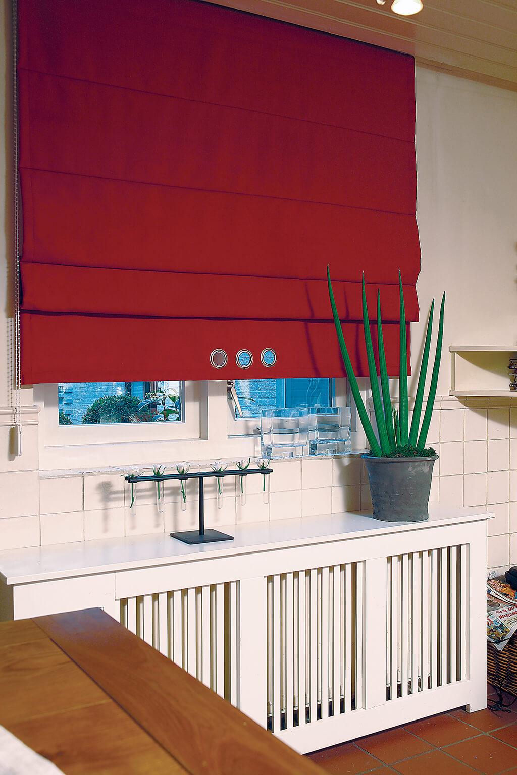 Rotes Faltrollo mit Querstreben und weißer Kunststoffkette als Bedienelement auf der linken Seite
