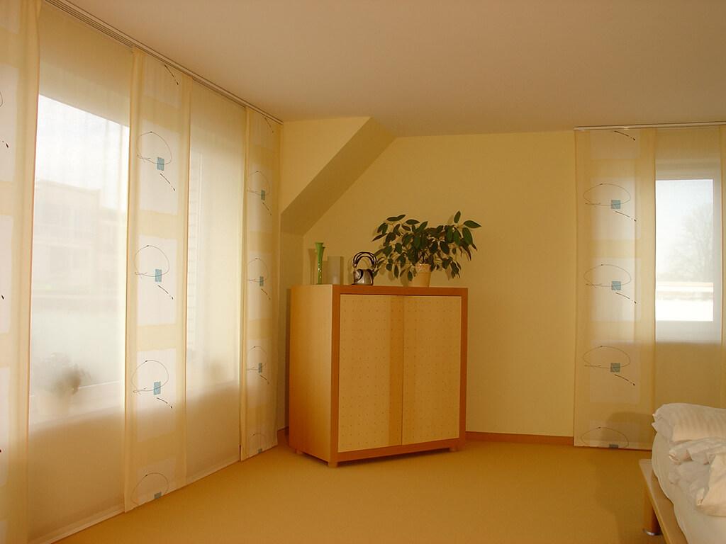 Flächenvorhang mit Dekorstoffpanelen, farblich abgestimmt zur gelben Ausstattung