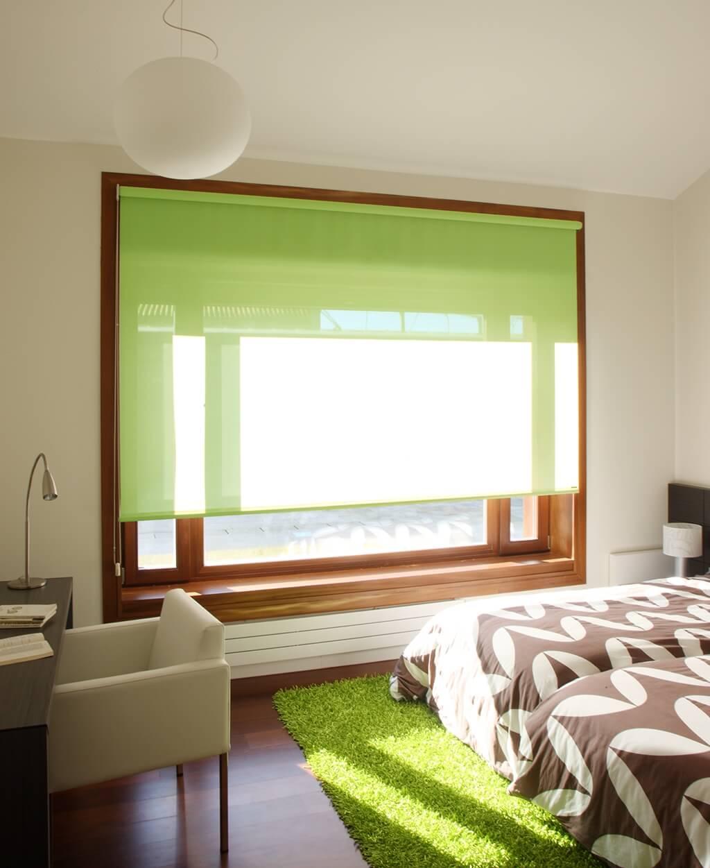 Rollo Bandalux in Grün an großem Schlafzimmerfenster mit dunklem Holzrahmen