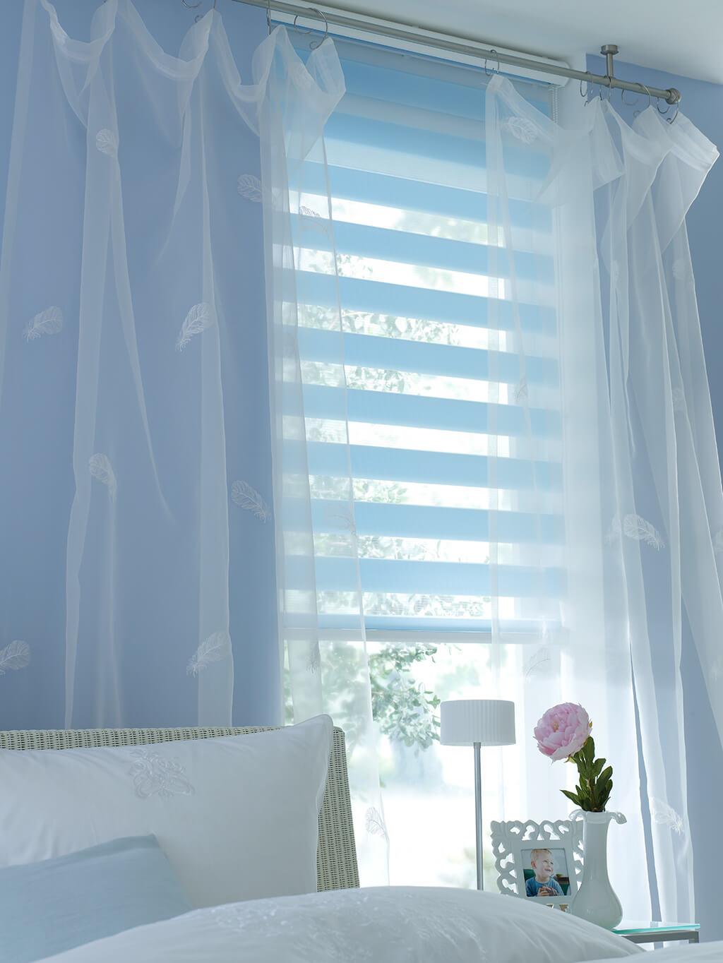 Hellblaues Doppelrollo zu sehr feiner tranparent-weißer Gardine