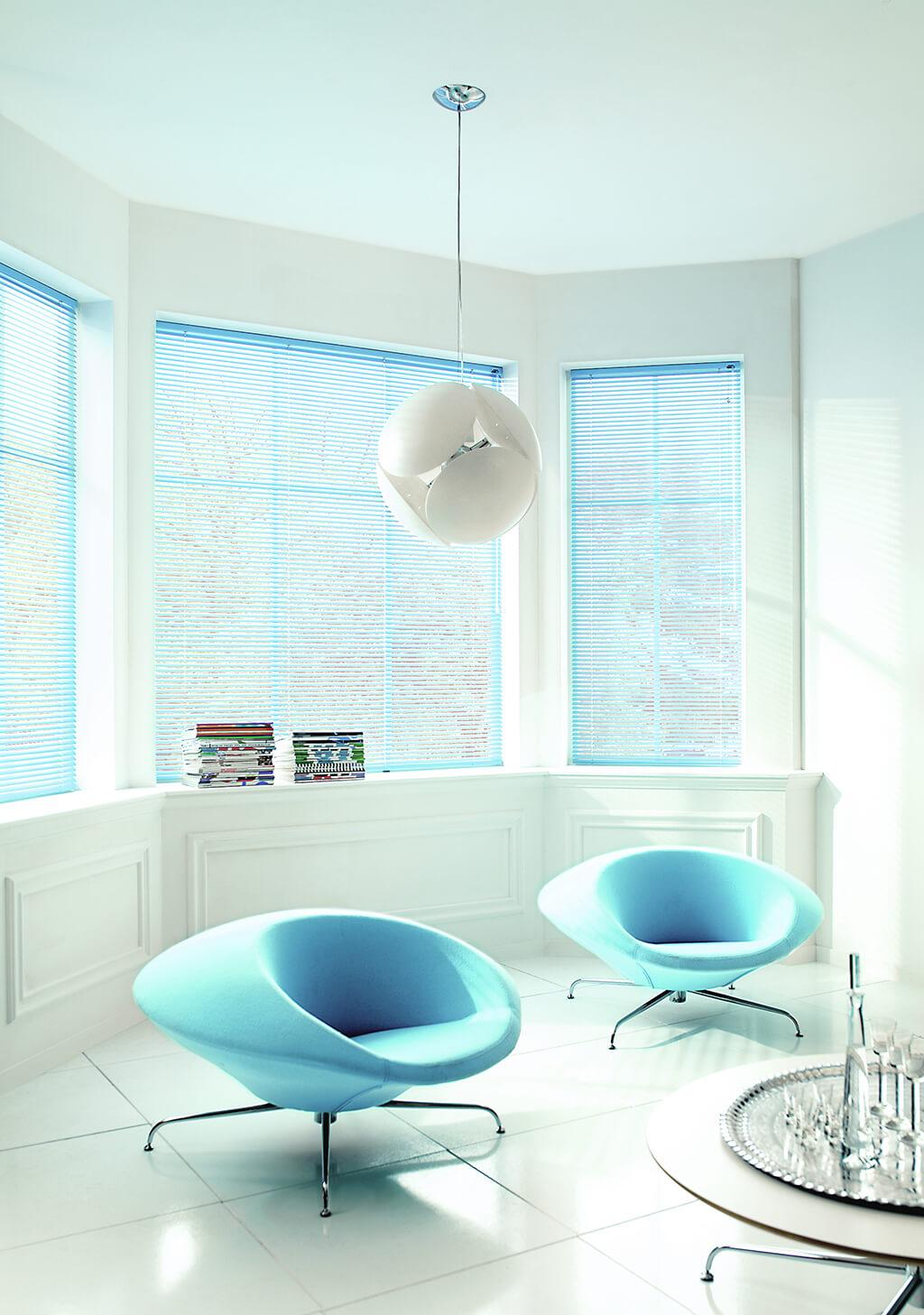 Hellblaue Alu-Jalousie mit schmalen Lamellen an Erkerfenstern im weiß-blau gehaltenen Wohnzimmer