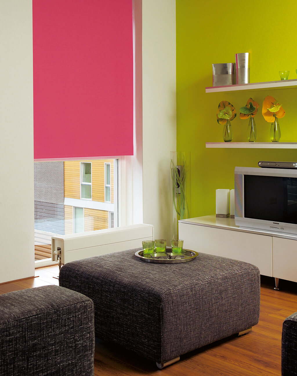 Pinkes Verdunkelungsrollo am deckenhohen Fenster im Wohnzimmer