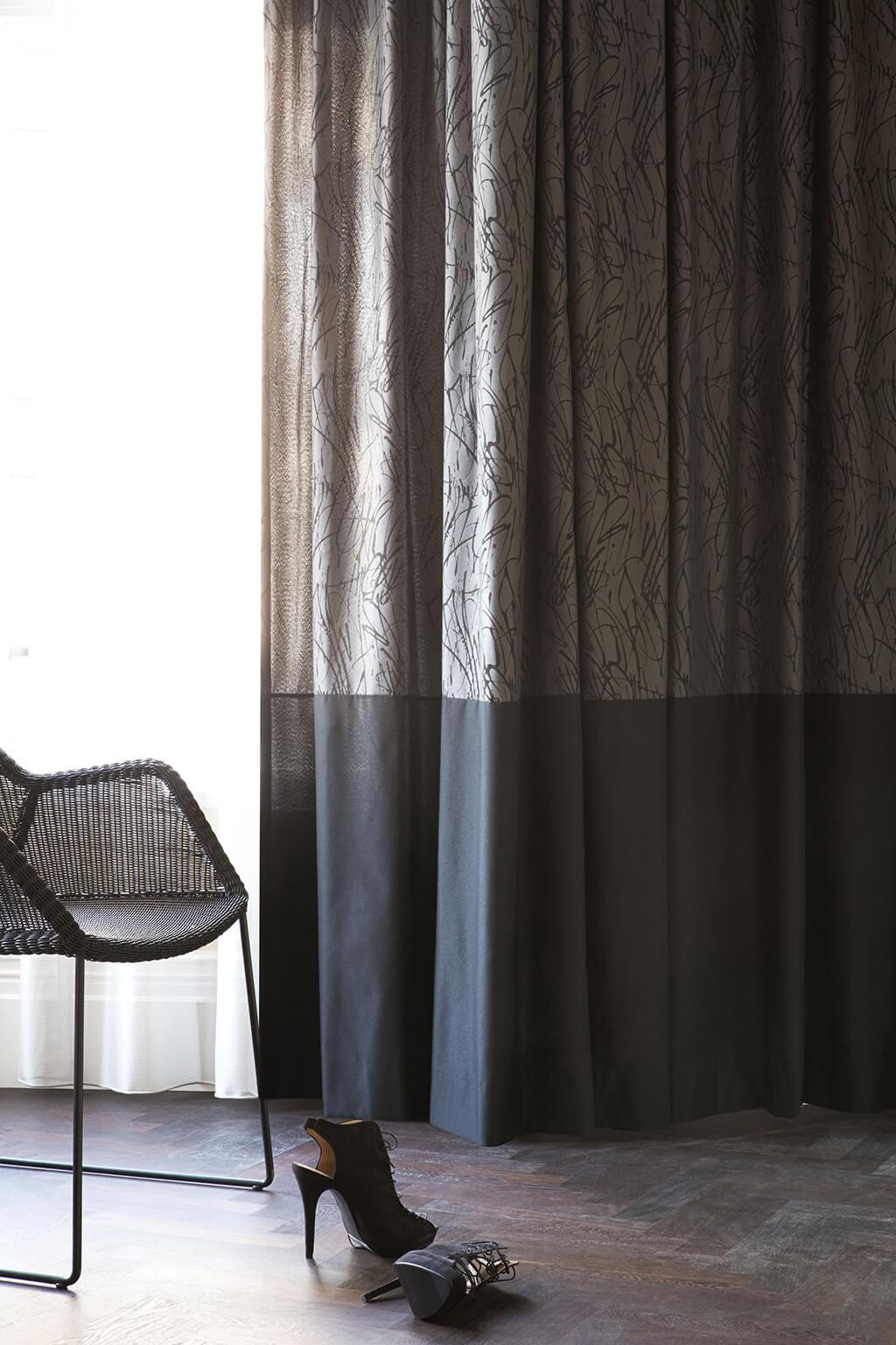 Dekorativer Vorhang aus beigem Dekorstoff mit schwarzem Absatz, zur tranparent weißen Gardine